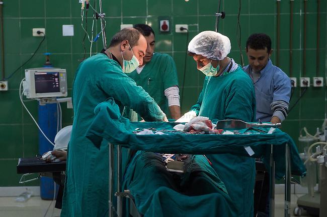 Hospital in Derik, Rojava/Syrien.<br /> Trotz etlichen kaputten Geraeten ist das Krankenhaus in Derik eines der bestausgeruesteten Hospitaeler im Kanton.<br /> Im Bild: Aerzte operieren eine schwerverletzte Kaempferin der YPG/YPJ, die bei den Kaempfen in der Stadt Haseker durch einen Schuss in den Ruecken lebensgefaehrlich verletzt wurde. Die Kugel drang bis in den Bauch und verletzte mehrere Organe. Den Aerzten gelang es ihr Leben zu retten.<br /> 17.12.2014, Derik/Rojava/Syrien<br /> Copyright: Christian-Ditsch.de<br /> [Inhaltsveraendernde Manipulation des Fotos nur nach ausdruecklicher Genehmigung des Fotografen. Vereinbarungen ueber Abtretung von Persoenlichkeitsrechten/Model Release der abgebildeten Person/Personen liegen nicht vor. NO MODEL RELEASE! Nur fuer Redaktionelle Zwecke. Don't publish without copyright Christian-Ditsch.de, Veroeffentlichung nur mit Fotografennennung, sowie gegen Honorar, MwSt. und Beleg. Konto: I N G - D i B a, IBAN DE58500105175400192269, BIC INGDDEFFXXX, Kontakt: post@christian-ditsch.de<br /> Bei der Bearbeitung der Dateiinformationen darf die Urheberkennzeichnung in den EXIF- und  IPTC-Daten nicht entfernt werden, diese sind in digitalen Medien nach &sect;95c UrhG rechtlich geschuetzt. Der Urhebervermerk wird gemaess &sect;13 UrhG verlangt.]