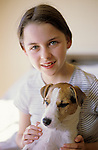 Jack Russell Terrier with young girl holding dog smiling at camera