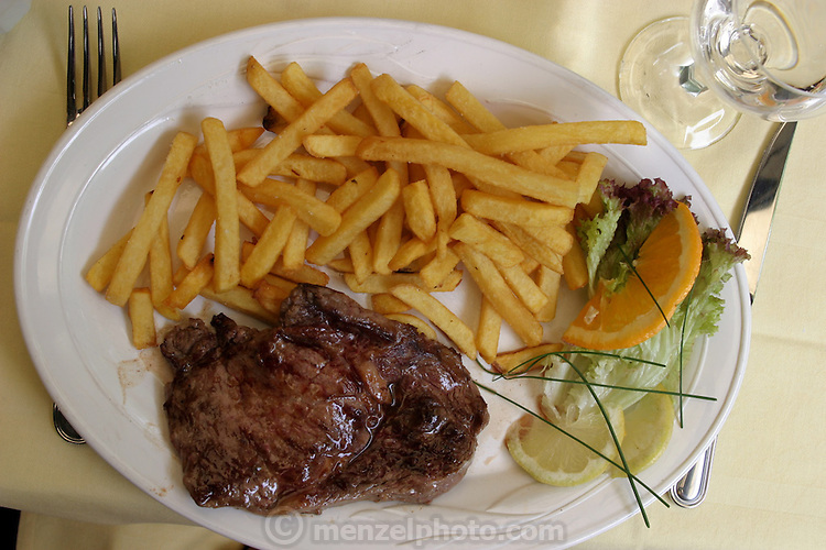 Grilled steak and fries for lunch in a restaurant on the Rue Maubourg, Paris, France. (Supporting image from the project Hungry Planet: What the World Eats)