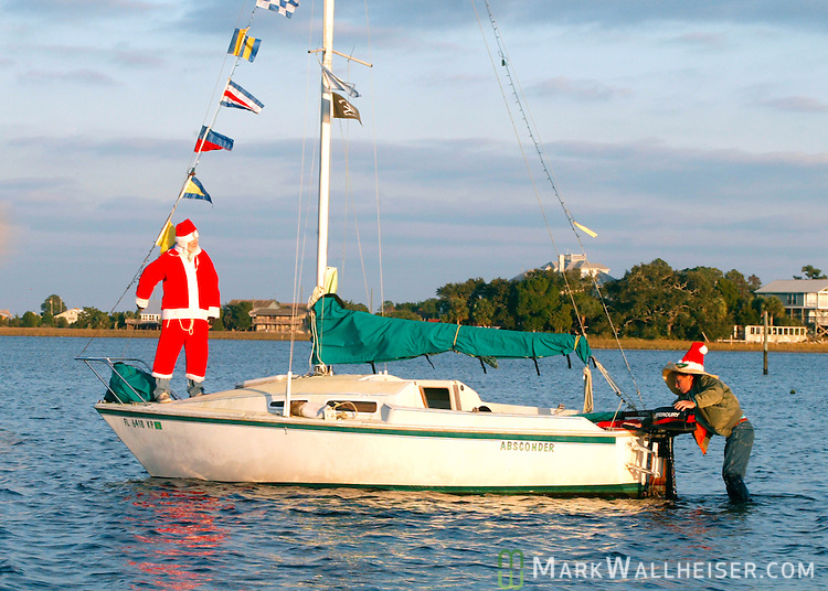 With their continued progress in the Shell Point Christmas Boat Parade hampered by a sand bar at low tide, helmsman and 'Mexican Elf' Steve Huffman (R) gets out to push the beached 'Sailboat Santa' , Joe Tillman, (L) free.  Shell Point is on the Gulf of Mexico 25 miles south of Tallahassee, Florida.   (Mark Wallheiser/TallahasseeStock.com)