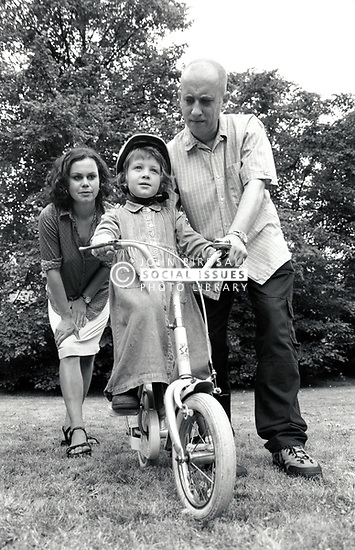 Parents with their daughter learning to ride a bike UK 1990s