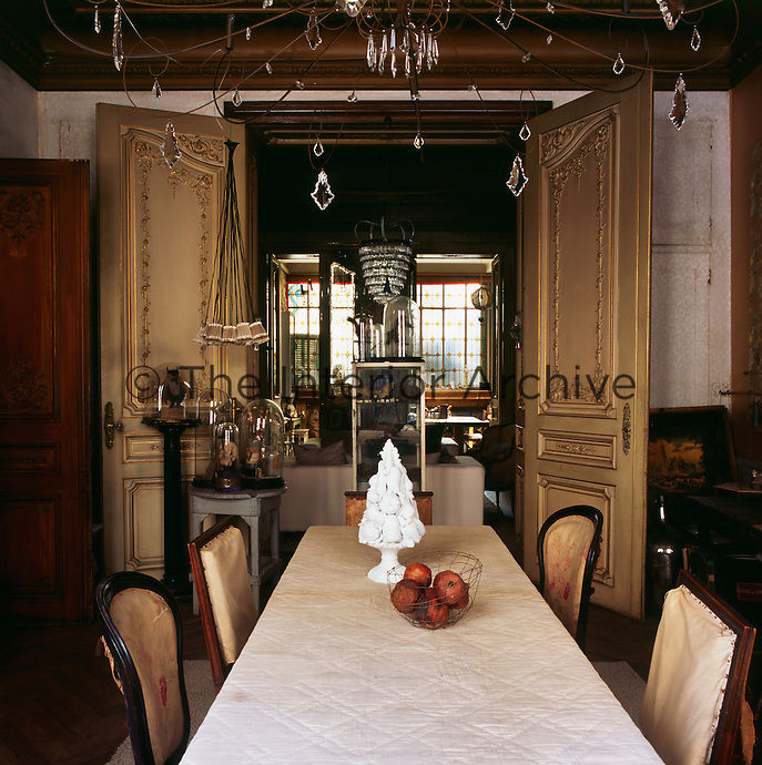 A traditional dining room with a set of ornate double doors opening onto a room beyond. A wire chandelier with glass drops hangs above the dining table and chairs.