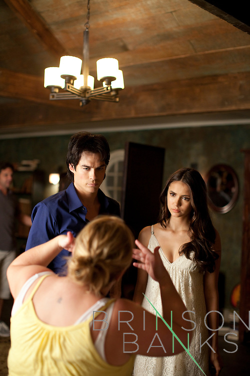 Actors Ian Somerhalder and Nina Dobrev talk to a writer on the set of the season three premiere of The Vampire Diaries in Decatur, Georgia July 18, 2011.