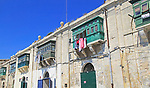 Old merchant house with balcony above warehouse area, Valletta, Malta