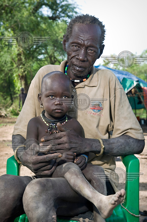 A grandfather and his granddaughter at a cattle camp near Tali village. Central Equatoria, South Sudan.