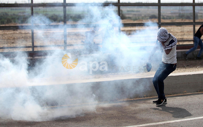 A Palestinian protester reacts from a tear gas canister fired by Israeli security forces during clashes next to the border fence with Israel, at the Erez crossing in the northern Gaza strip, on October 13, 2015. A wave of stabbings that hit Israel, Jerusalem and the West Bank this month along with violent protests in annexed east Jerusalem and the occupied West Bank, has led to warnings that a full-scale Palestinian uprising, or third intifada, could erupt. The unrest has also spread to the Gaza Strip, with clashes along the border in recent days leaving nine Palestinians dead from Israeli fire. Photo by Ashraf Amra