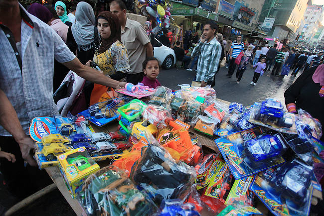 Palestinians shop at a street market in preparation for the upcoming Eid-al-Adha, or ''Feast of Sacrifice,'' in the West Bank City of Ramallah on October 13, 2013. Millions of Muslims around the world celebrate Eid al-Adha or Feast of the Sacrifice, which marks the end of the annual hajj or pilgrimage to Mecca and celebrates Abraham's readiness to sacrifice his son to God. Photo by Issam Rimawi