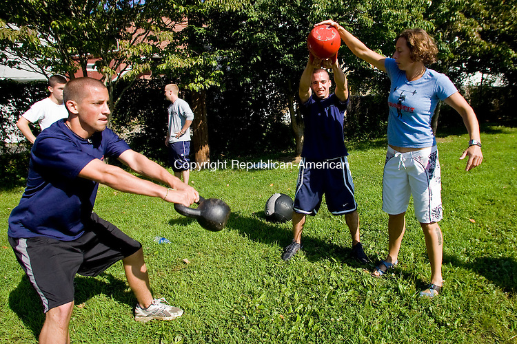 WATERTOWN, CT - 08 AUGUST 2009 -080809JT01-<br /> CrossFit Watertown's general manager Jen Conlin coaches Marine recruit Brandt Kittredge, of Torrington, as he and his workout teammate and fellow recruit Matt Walsh, left, of Watertown, do a training exercise with kettlebells provided by CrossFit at the facility in Watertown on Saturday. Almost 40 recruits participated in the free intensive exercise regimen provided to them by CrossFit.<br /> Josalee Thrift Republican-American