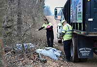 Teresa Sidwell, environmental manager (center) and Merced Cervantes, environmental officer (right) count discarded bags of Hydaul-EZ borehole stabilizer, Monday, February 10, 2020 along Logan Cave Rd. in Siloam Springs. Check out nwaonline.com/200211Daily/ for today's photo gallery.<br /> (NWA Democrat-Gazette/Charlie Kaijo)<br /> <br /> A cleanup crew from the Environmental Division for Benton County Government picked up illegally discarded waste products. <br /> <br /> Teresa Sidwell, environmental manager, said a lot of times people are trying to avoid having to pay to take it to the land fill, but added, they have a program where people can drop off large waster products for free.