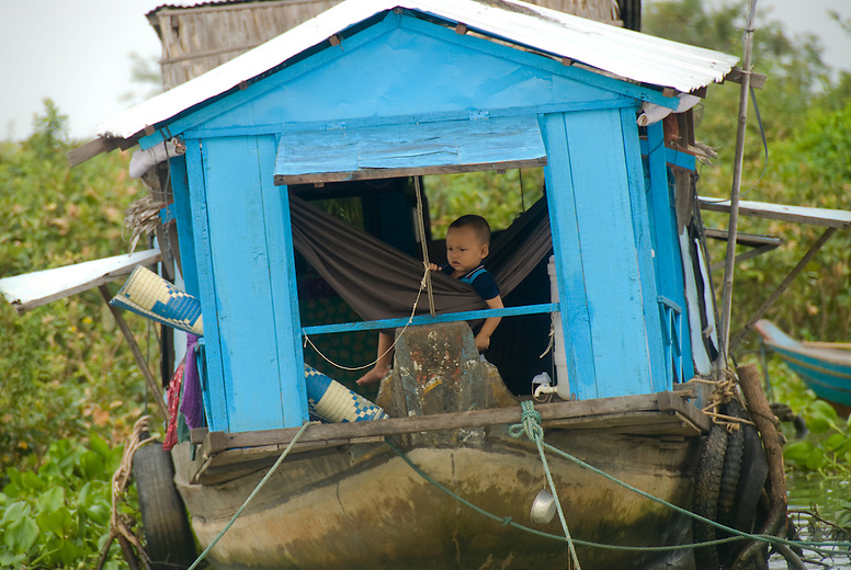 Vietnamese families living in boats along the floating village near Siem Reap, Cambodia. A boy peers through a window on the Vietnamese floating village near Siem Reap, Cambodia. The Vietnamese floating villagers on branches of Lake Tonie Sap, Cambodia are a unique nomadic community. With permission from the Cambodian government, they have built an entire floating community of houseboats, churches, clinics, shops and community centers on the river near Siem Reap, Cambodia. As the seasons change and the tides shift the entire village changes its location. The villagers rely on sales of fruits and soft drinks to the many tourists who have come by boat to see firsthand the hardships of life on a floating village. The Vietnamese are the most vulnerable of Cambodia's minorities, and the most prone to discrimination and violations of their rights.