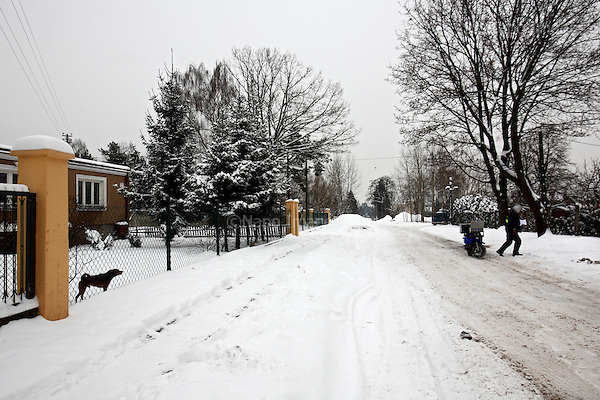 Dog watching 60-years old Polish postman Jacek Szczerba in snow covered Piaseczno in central Poland. Jacek is celebrating 40-th anniversary of his work as a postman..January 2010.(Photo by Piotr Malecki / Napo Images)..Praca listonosza. Pies patrzy na przechodzacego Jacka. Jacek Serkiew wlasnie obchodzi czterdziestolecie pracy na tym stanowisku. .Piaseczno, Styczen 2010.(Photo by Piotr Malecki / Napo Images) ..