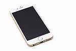 Gold white Apple iPhone 6 6s with blank black display lying isolated on white background