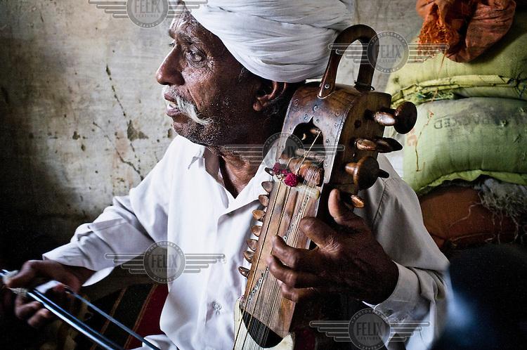 66 year old Manganiyar folk musician, Lakha Khan, plays the Sarangi (a short-necked stringed instrument) at his home in Raneri Village.