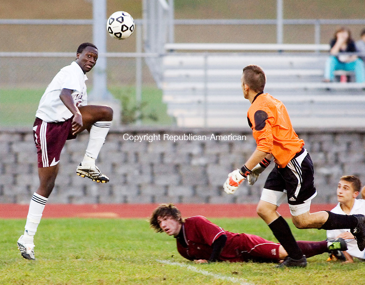 NAUGATUCK, CT- 03 OCT 2007- 100307JT18- <br /> In a rush toward the goal, Naugatuck's Matt Carreira jumps into Torrington's Kyle Briggs, both of them falling down afterwards, while Naugatuck's Emanuel Nanadoum, left, scored a goal past Torrington goalie Justin Duksis, foreground, during  Wednesday's game atNaugatuck, which ended 1-1 after overtime. <br /> Josalee Thrift / Republican-American