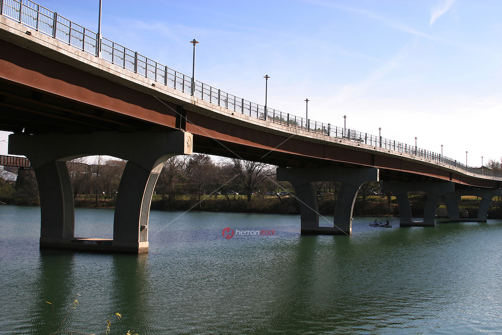 Runners and joggers run on top of the Lamar Pedestrian Bicycle Bridge on the Hike and Bike Trail on Town Lake in Austin.