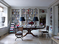 The bookshelves and ladder in the library are custom-made and the airy brass lamps on the dining table were designed so guests can see through them and they don't hinder conversation