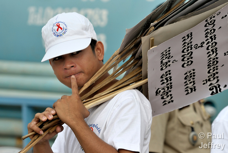 A man carries signs to be distributed to participants in a march to commemorate World AIDS Day in Battambang, Cambodia. Among sponsors of the march was the Salvation Centre Cambodia, an organization that works with Buddhist monks and other activists to foster support for people living with HIV and AIDS as well as public education and advocacy throughout the country.