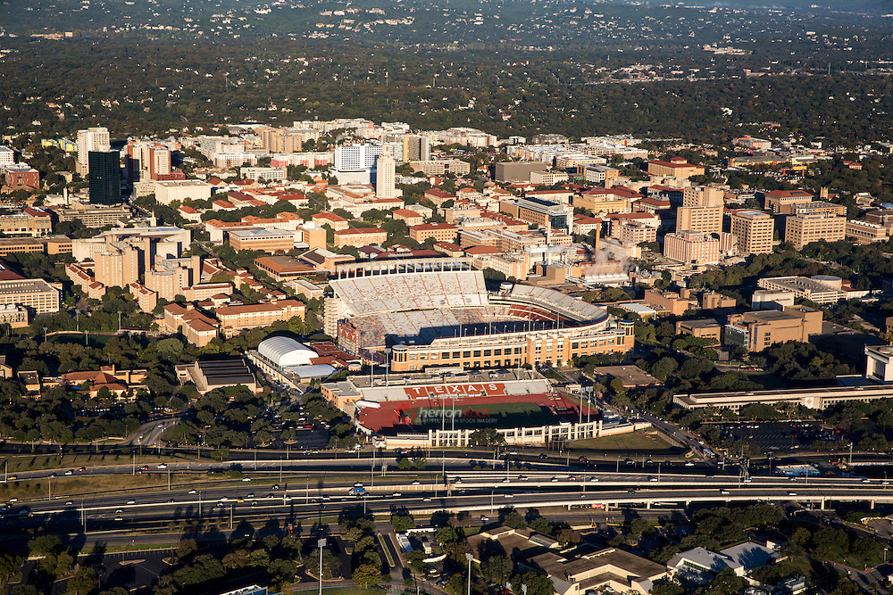 Beautiful aerial helicopter view of the Darrell K Royal University of Texas Memorial Football Stadium amid the backdrop of the majestic University of Texas Campus in Austin, Texas.