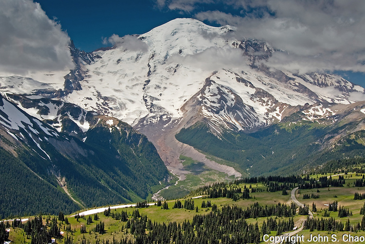 Upper Sunrise Road winds its way through alpine meadows and evergreen trees below Mount Rainier, an active volcano whose summit is at 14,410 feet elevation. Taken above the Sunrise area, Mount Rainier National Park, Washington State.....Photographed on digital media.