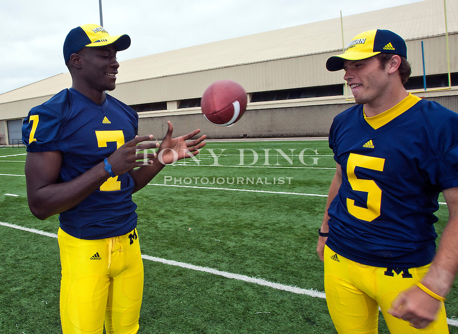 Michigan quarterback Devin Gardner (7) juggles the ball with fellow quarterback Tate Forcier (5) at the annual NCAA college football media day, Sunday, Aug. 22, 2010, in Ann Arbor, Mich. (AP Photo/Tony Ding)