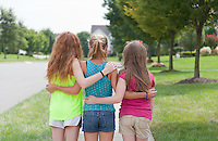 Three Young Girls in a Row, Arm in Arm, looking out at their Residential Neighborhood