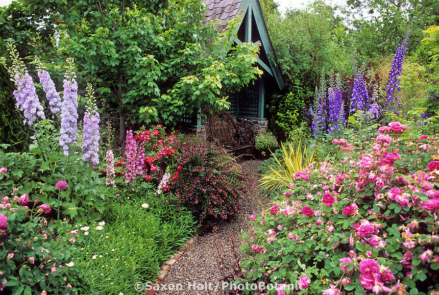 Delphiniums and Roses surrounding secluded sitting area in perennial garden.  CREDIT: FREELAND TANNER