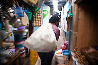 Entreprenuer Mary Cherop Maritim leaves the market after buying maize in Kangemi slum where she started her business packaging pre-cooked then frozen, Kenyan staples.