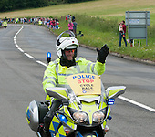 Police motorcyclists wave to the crowds.  Olympics 2012.  Women's cycle road race passes along the Shere bypass, the A25, on it's way to Box Hill and then back to the finish in London.