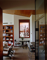 The furniture in the family room echoes the geometric lines of the house and the window perfectly frames the landscape outside