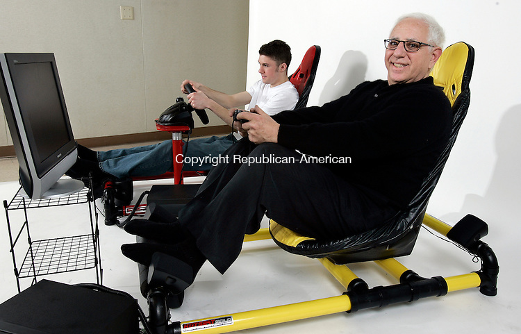 PLYMOUTH, CT. 05 APRIL  2005--040505SV01--from left; Jared Wheeler trys out a seat for videogame players with Jay LeBoff the inventor of the seat at LeBoff's business in Plymouth Tuesday. Steven Valenti Photo<br /> (Jared Wheeler,(cq),Jay LeBoff,(cq))