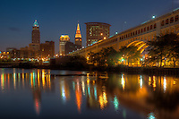 The skyline of Cleveland, Ohio reflects off the surface of the Cuyahoga River during morning twilight.