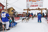 Karin Hendrickson runs under the burl arch finish line in Nome on Thursday March 13 during the 2014 Iditarod Sled Dog Race.<br /> <br /> PHOTO (c) BY JEFF SCHULTZ/IditarodPhotos.com -- REPRODUCTION PROHIBITED WITHOUT PERMISSION