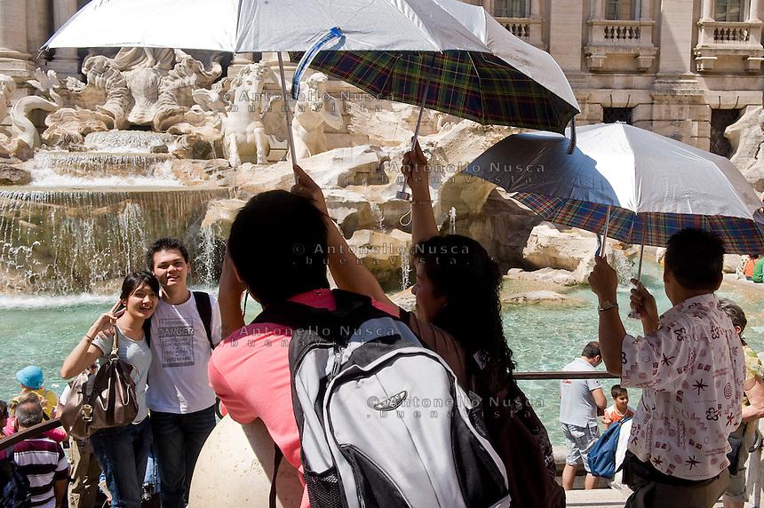 Rome continue to be one of the most visited city in the world..Roma continua ad essere una delle città più visitata al mondo.Tourists taking photos in front of the Trevi fountain