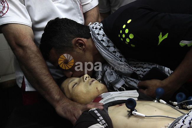 A Palestinian relative kisses the body of 14-year-old Mohammad Jihad Dodeen at Alia Hospital after reportedly being shot to death by Israeli soldiers in Doura village, in the West Bank town of Hebron, June 20, 2014. In the early morning Israeli soldiers entered Doura village arresting Palestinians during a military search operation. Photo by Mamoun Wazwaz