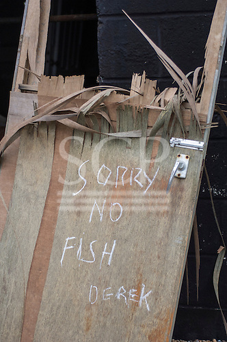 Hastings,  East Sussex, England. Winter.  Sorry no fish, Derek,  sign on a broken wooden  door. Stade beach.