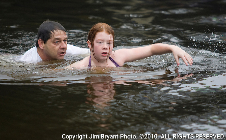 Dave Otto (L) helps his 12-year-old daughter, Madeline, out of the water after   they leaped into the Burley Lagoon during the 25th annual Polar Bear jump in Olalla, Washington on January 1, 2009. This was a first time leap for both of them.Jim Bryant Photo. ©2010. ALL RIGHTS RESERVED.