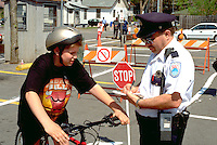Officer writing ticket to teen at community Youth Express Bicycle Safety Rodeo.  St Paul Minnesota USA