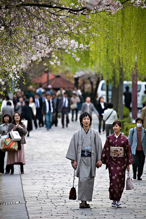 Traditionally dressed couple walking down side street in Kyoto Japan