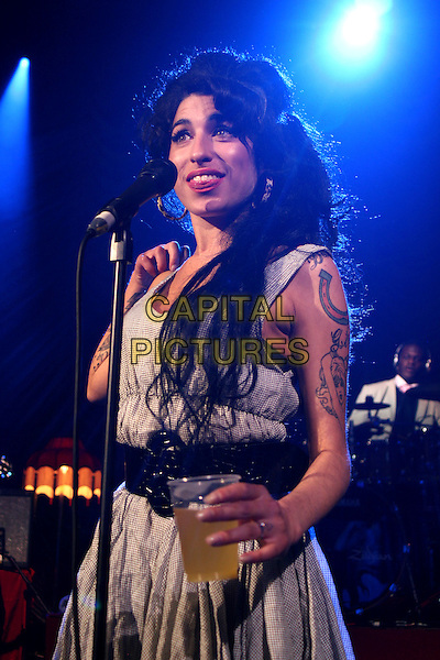 AMY WINEHOUSE.Live in concert at the Shepherd's Bush Empire, London, England..May 28th, 2007.gig performance music half length grey gray dress back belt drink cup glass beverage tattoos .CAP/MAR.© Martin Harris/Capital Pictures.