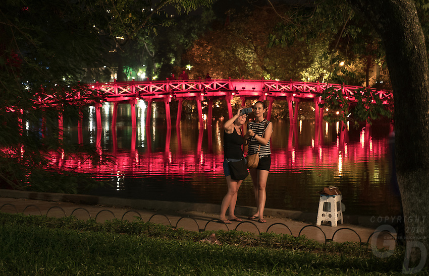 European Tourist taken a Selfie photo in front of the red The Huc Bridge in Hanoi.