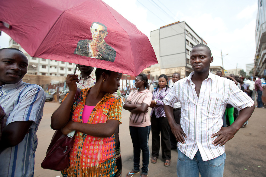 Friday 18 february 2011 - Kampala, Uganda - An Ugandan woman holds an ombrella with a print of American President Barack Obama. She is waiting online with others Ugandan citizens to cast their ballots at a polling station in Kampala. Ugandans vote on Friday in elections expected to return long-serving President Yoweri Museveni to power, with a fragmented opposition crying foul even before the ballot. Photo credit: Benedicte Desrus
