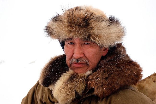 Yuri Ilkay, an elderly Chukchi, dressed in traditional winter clothes. Uelen, Chukotka, Siberia, Russia.