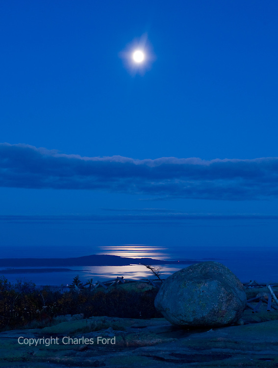 Moonrise over the Atlantic with rocks in foreground.  Taken from summit of Cadillac Mountain, Acadia National Park, Maine. Vertical crop.