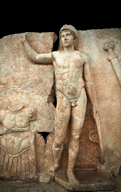 Close up of a Roman Sebasteion relief  sculpture of Ares, Aphrodisias Museum, Aphrodisias, Turkey.   Against a black background.<br /> <br /> The nude and classically7 styled young god wears only a helmet and holds a spear (missing) in one hand and a shield in the other. At the left stands cuirass, and at the upper right corner hangs his sword. Ares was a god of war and was not later defaced by Christians probably because he so closely resembles a young emperor.