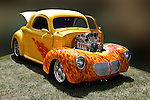 This Willys Coupe stands out with its bold gold body, no cover over its highly polished, chrome engine and flames painted on the fenders and door panels. The fun car stands on in sun-sparkled grass  aganst a blurred, dark-colored background camouflaging the environment at the 2010 Wings 'n' Wheels Showcase, Galway, New York.