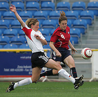 MAR 15, 2006: Faro, Portugal:  USWNT forward (9) crosses the ball in front of German midfielder (17) Melanie Behringer in the finals of the Algarve Cup in Faro, Portugal.