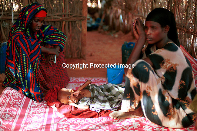 dicoeth00030.Ethiopia. A dying young boy on April 14, 2000 with his mother at a feeding center in Gode, Ogaden Province in Ethiopia. They have come from the country side looking for food and water. The region was hit by severe drought in the spring of 2000..©Per-Anders Pettersson/ iAfrika Photos