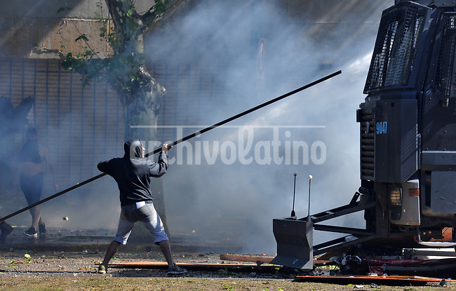A rioter attacks a water cannon during severe clashes   near the Congress building while Deputies Chamber was   discussing changes in   retirement legislation