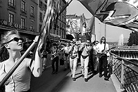 Switzerland. Geneva. A band is walking in the streets on Music Day. The drummer is carried on a platform by four muscular men. Guitar and bass players. A woman marches in front and holds a flag. In the background, the Jet d'Eau (Water-Jet) which is the city's most famous landmarks. Situated at the point where Lake Geneva empties into the Rhône, it is visible throughout the city and from the air. Five hundred litres of water per second are jetted to an altitude of 140 meters by two 500 kW pumps, operating at 2,400 V, consuming one megawatt of electricity. The water leaves the 10 cm nozzle at a speed of 200 kilometers per hour. At any given moment, there are about 7,000 litres of water in the air. The Fête de la Musique, also known in English as Music Day, Make Music Day or World Music Day, is an annual music celebration that takes place on 21 June ( but usually during the previous or following weekend). On Music Day the citizens of a city or country are allowed and urged to play music outside in their neighborhoods or in public spaces and parks. Free concerts are also organized, where musicians play for fun and not for payment. 22.06.1993 © 1993 Didier Ruef