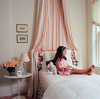 Philip Gorrivan's daughter sits on her bed in a very feminine and rather glamorous bedroom